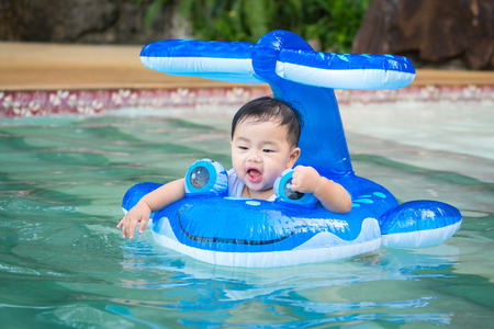 Asian baby play a water and swimming in swimming pool