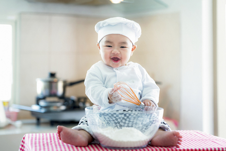 Asian baby in kitchen, newborn baby concept for job, career, occupation and dream. Food, cooking, bread and bakery concept Banco de Imagens
