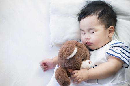 Noworodek śpi z misiem na łóżku