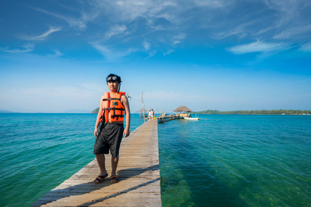 Asian man with snorkeling mask walking on the wooded bridge to the harbor in Koh Mak, Koh Mak and Kood is island and sea in Thailand
