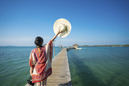 Asian lady walk in wooded bridge to harbor in Koh Mak, Mak and Kood island is travel place in Thailand, This image can use for Holiday, summer, beach, sea and travel concept
