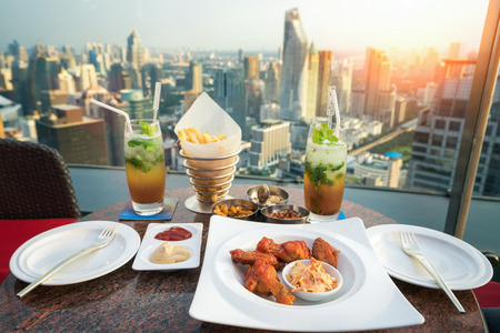 Food, snacks and mojito cocktail on the deak in rooftop bar in Bangkok city, Thailand