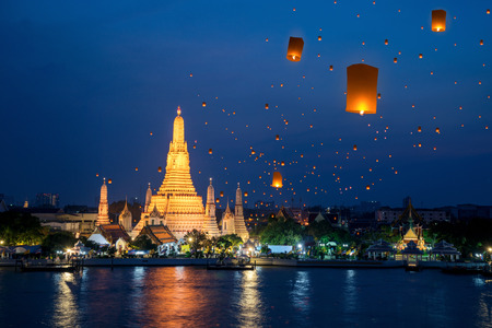 Wat Arun temple on night in Bangkok city with yeepeng float lantern background, this immage can use for Thailand travel and new year celebration in Thailand.