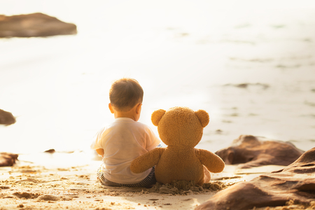Baby and teddy bear sit togather on the beach, this immage can use for kid, friend, love, travel, lone and family concept 版權商用圖片