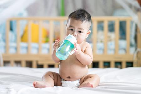 Bébé asiatique boire de l'eau par une bouteille en plastique dans la chambre Banque d'images - 97950239