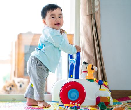 Bebé asiático que entrena caminando con el juguete del caminante.
