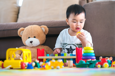 Asian boy play a toy with teddy bear in lieving room, this immage can use for fun, toy, baby, education, home, family, child concept Stockfoto