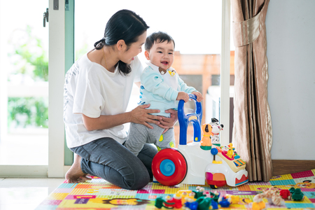 Asian mother and baby training walking with walker toy. This immage can use for baby, family, education, and play concept. Foto de archivo
