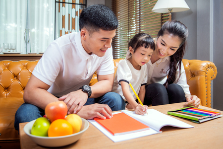 Asian father, mother and daughter doing home work togather in living room, this immage can use for education, home and family concept Standard-Bild
