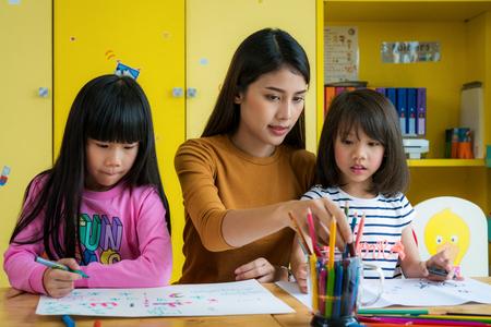 Maestra asiática y estudiante de preescolar en la clase de arte, esta imagen se puede usar para el concepto de maestro, educación, escuela, estudiante, niño, arte y regreso a la escuela.