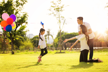 Asian family run and play in a garden, this immage can use for father, mother, kid and summer concept