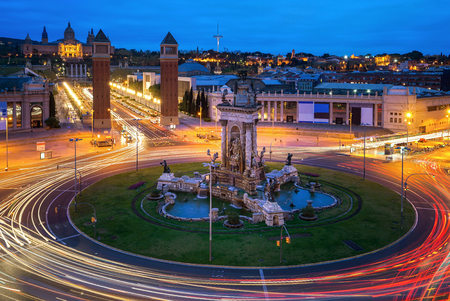 Spanish Square aerial view in Barcelona, Spain at night. This is the famous place with traffic light trails, fountain and Venetian towers, and National museum at the background. Blue sky 免版税图像