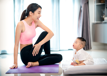 Mother in yoga action and baby in home, this photo can use for healthy,exercise, fitness, yoga, and family concept Stock Photo