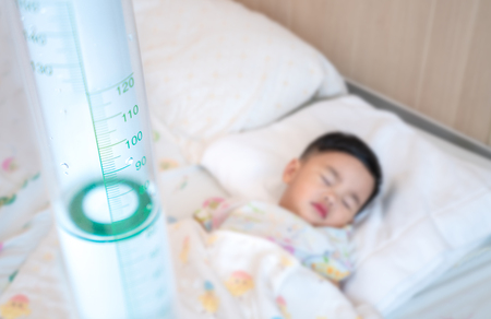 Asian kin sick from influenza and sleep with saling on the bed in Hospital, this picture can use for patirnt, health, flu, faver, insurance and hospital Stock Photo