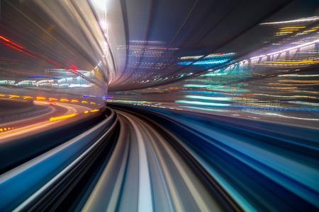 Motion blur of a city and tunnel from inside a moving monorail in Tokyo. Abstract motion speed railway tunnel with city background