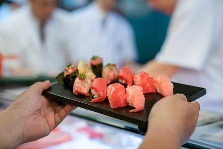 Cliente toma Salman Shushi del chef en un restaurante de marisco japonés Foto de archivo