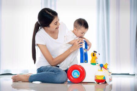 Aziatische moeder die naar haar baby loopt door met speelgoed te lopen Stockfoto