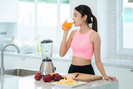 Señora asiática beber una mezcla de frutas para la salud en una sala de kitvhen