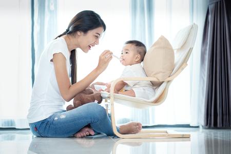 Aziatische moeder voedt haar baby in de levingskamer