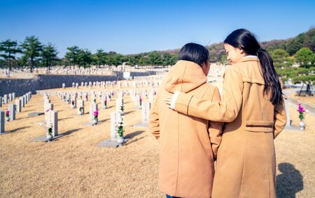 Korean people infront of tombstone in tomb of Korea war, ombstones in Seoul National Cemetery, Seoul city, South Korea