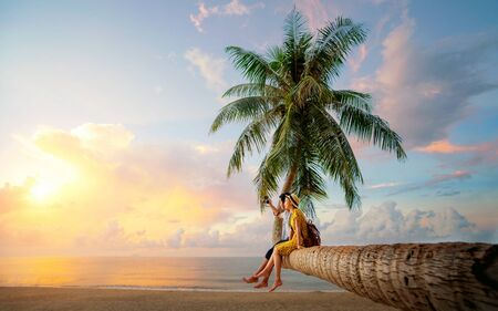 Asian couple selfie by camera on coconut palm tree in Kho Mak island, Kood, Trat, Thailand, this image can use for summer, beach, travel and valentine concept