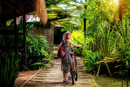 Asian lady rent a bicycle in tropical resort in Koh Mak, Trat, Thailand, this image can use for travel, relax, and holiday concept Imagens