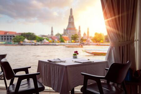 Wat Arun temple, view point from the river side bar in Bangkok, Thailand, this image can use for Travel, restaurant and romantic concept Фото со стока