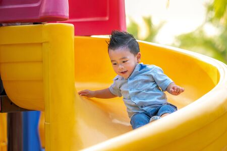 Asian boy smile and play slider in playground in a park