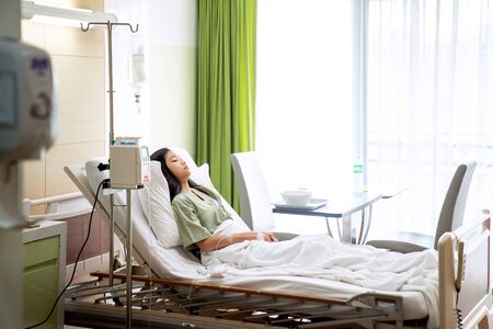 Señora asiática que duerme y paciente en el hospital con solución intravenosa, esta imagen se puede utilizar para el concepto de gripe, enfermedad, salud, medicina y medicina Foto de archivo