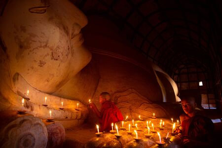 Monk in Bagan old town pray a buddha statue with candle, bagan city, Myanmar Stockfoto