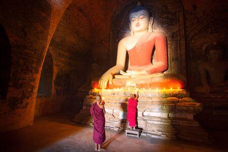 Mönch in alter Stadt Bagan beten eine Buddha-Statue mit Kerze, Bagan-Stadt, Myanmar Standard-Bild
