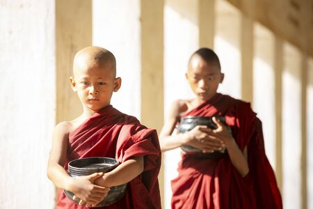 Buddhism novices are walking with umberella in temple, Bagan, Myanmar