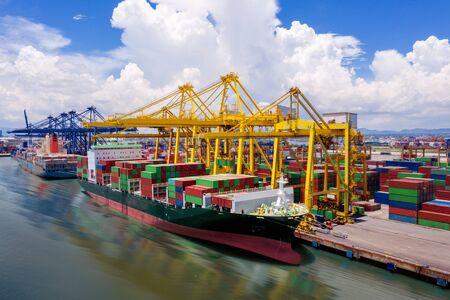 Logistik und Transport von Containerfrachtschiffen und Frachtflugzeugen mit funktionierender Kranbrücke in der Werft bei Sonnenaufgang, logistischer Importexport- und Transportindustriehintergrund, Luftbild von Drohne Standard-Bild
