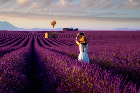 Asian girl travel in lavender field in France and take photo a hot air balloon with sun set background. Imagens
