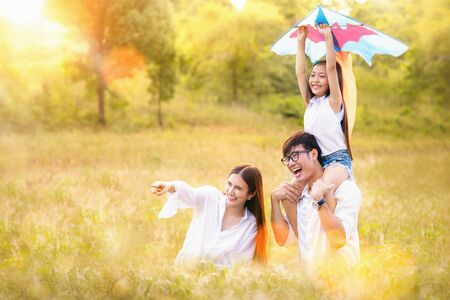 Asian family father, mother and daughter play ta kite in the outdoor park with sunrise and golden colour, this image can use for family, relax, freedom, summer and travel concept