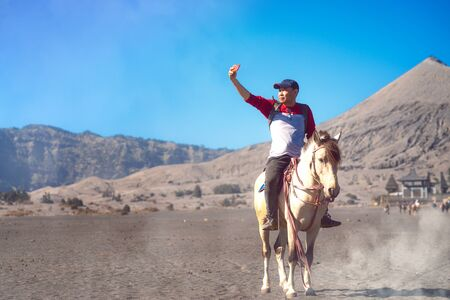 Asian traveller use smartphone selfie on between ride a horse at Bromo mountain national park, Java island, Indonesia