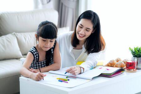 Mutter unterrichtet asiatische Vorschulschüler, die Hausaufgaben machen, indem sie nach einer Farbe reiben. Dieses Bild kann für Mädchen, Studium, Schule, Mutter, Lehrer, Kind, Schüler und Bildungskonzept verwendet werden