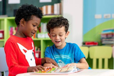 Schüler in der internationalen Vorschule, die zusammen ein Zeitschriftenbuch in der Schulbibliothek, Bildung, Kinder- und Studienkonzept lesen