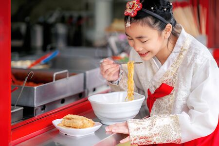 Korean girl eat a noodle with Korean traditional dress in old and vintage restaurant, seoul city, south korea