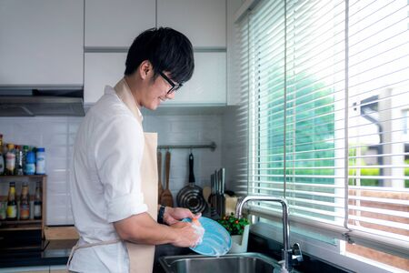 Hombre asiático sonríe y lava un plato en la cocina, esta imagen se puede utilizar para el concepto de marido, trabajador, trabajo y limpieza