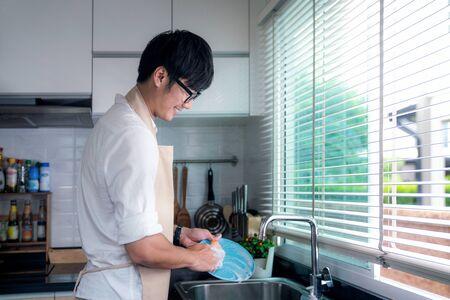 Un homme asiatique sourit et lave un plat dans la cuisine, cette image peut être utilisée pour le mari, le travailleur, le travail et le concept de nettoyage