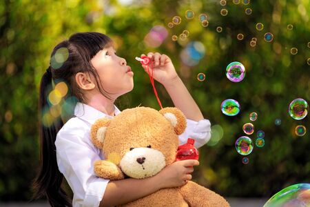 Asian girl play a bubble from soap in out door park, this photo can use for kid, play and chid concept
