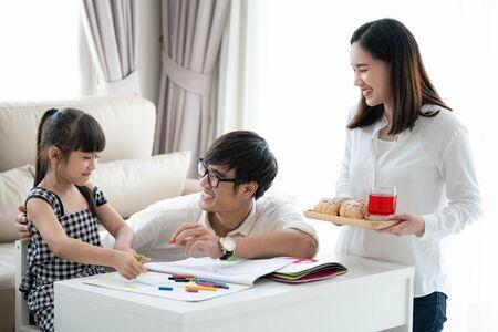 Asiatische Familie macht Hausaufgaben zusammen im Wohnzimmer, dieses Bild kann für Bildung, Schüler, Vater, Mutter und Heimkonzept verwendet werden