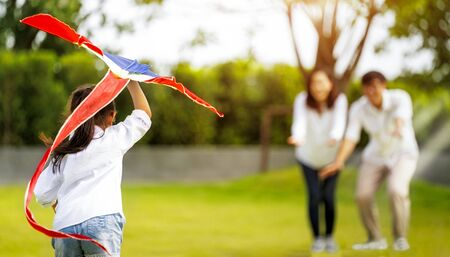 Asian family father, mother and daughter play a kite in the outdoor park in village near thay home, this image can use for family, relax, freedon, summer and travel concept