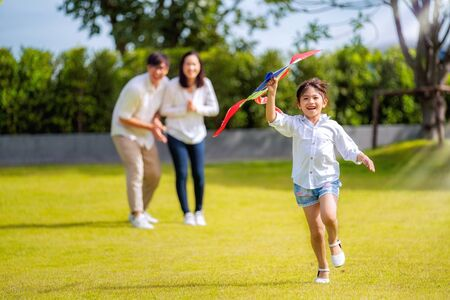 Asian family father, mother and daughter play a kite in the outdoor park in village near thay home, this image can use for family, relax, freedon, summer and travel concept Banco de Imagens