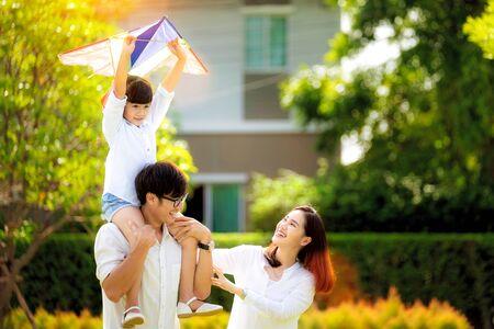 Padre di famiglia asiatico, madre e figlia giocano un aquilone nel parco all'aperto nel villaggio vicino a casa, questa immagine può essere utilizzata per la famiglia, il relax, la libertà, l'estate e il concetto di viaggio