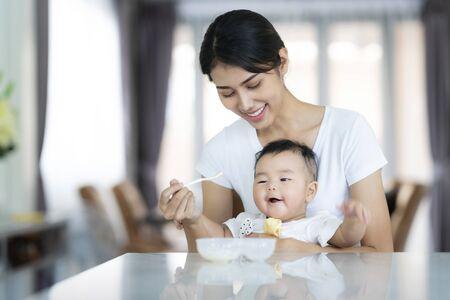 아시아 어머니는 아기에게 수프를 먹이며 이 이미지는 아기, 소년, 엄마, 가족 개념에 사용할 수 있습니다.