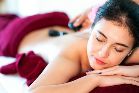 Asian girl sleep and relax with rock hot spa in thailand resort, this image can use for massage, spa, relax and aroma therapy