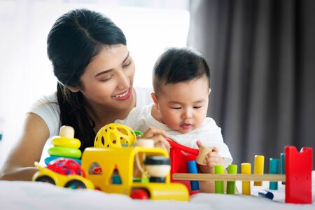 Asian mother and baby play togather with wooded toy in bed room, this image can use for boy, mom, study, education and mother's day concept