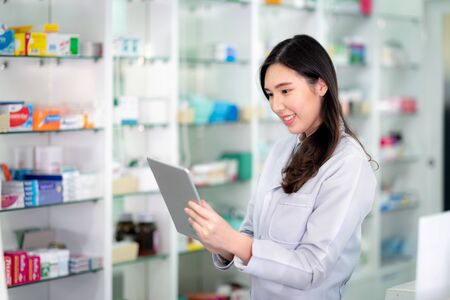 Asian Pharmacist girl use tablet pad computer for check stock of phamacy in her drugstore, this image can use for hospital, clinic, lab and internet concept